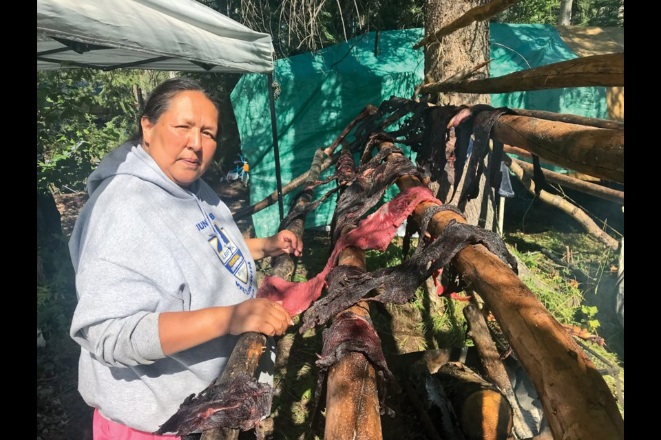 Tracy Paquette hangs moose meat to dry at a camp near the Blueberry River First Nation, July 18, 2020.