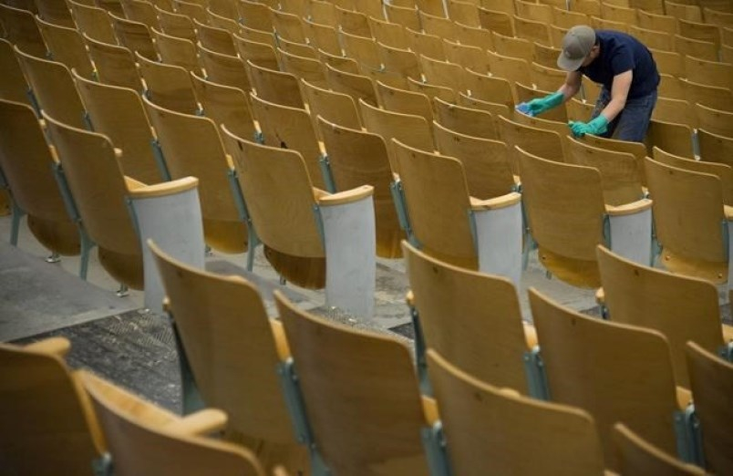 A worker cleans the seats of the auditorium at Eric Hamber Secondary school in Vancouver, B.C., Mond