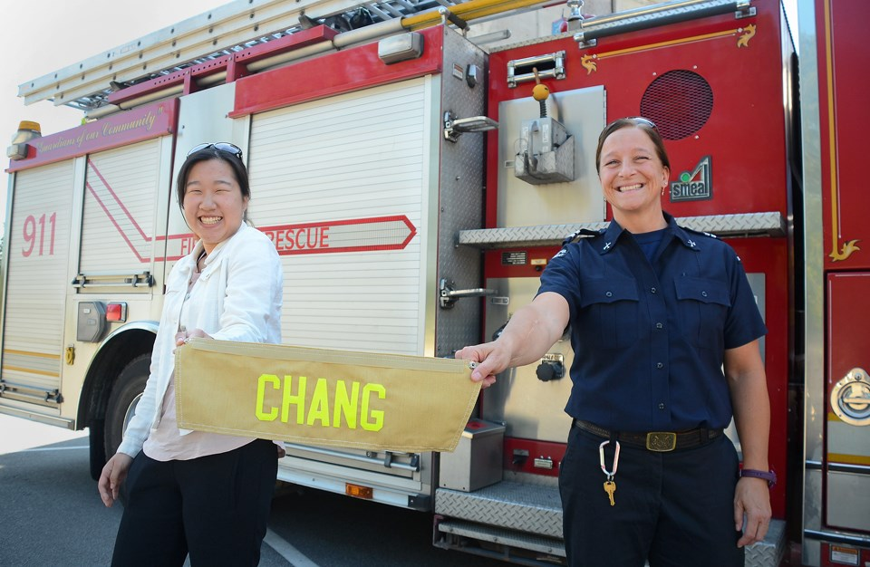 Byrne Creek Community School grad Irene Chang and Burnaby Fire Department Lt. Heather Wilson show off the personalized name bar Chang will wear on the back of her turnout gear at Camp Ignite, an all-girls firefighting camp this weekend.