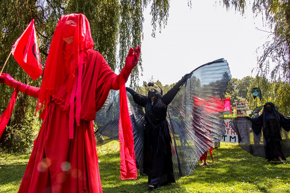 Members of the Red Brigade perform for a crowd of protesters at an Extinction Rebellion protest against the Trans Mountain pipeline expansion and planned construction in the Brunette River conservation area.