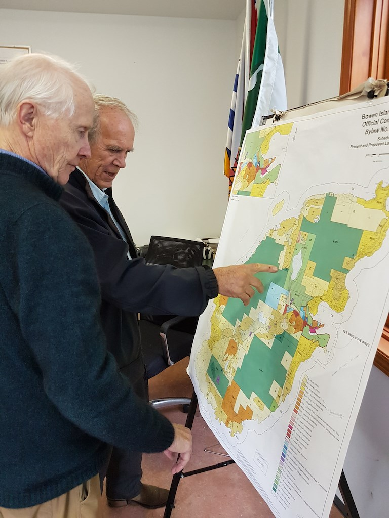 Two men looking at a patchwork map of Bowen