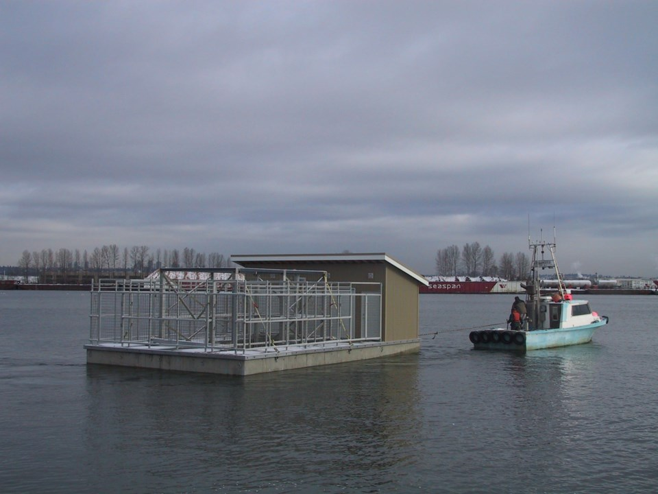 One of the sea lion pens and a shed get towed away from Reed Point Marina to a temporary moorage. It