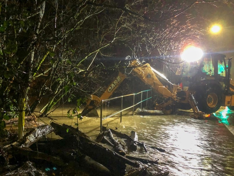 A backhoe from Port Coquitlam public works tries to dislodge debris from a flooded culvert as flooding from Hyde Creek spills into six homes along Coast Meridian Road, including one which doubles as a daycare. Scenes like this would become more common in the Tri-Cities as climate change triggers more flooding events in several vulnerable neighbourhoods.