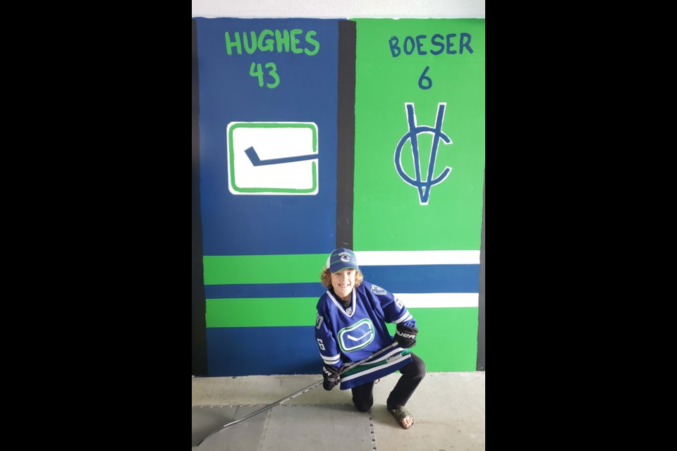 Ryder Starchuk, 8, with his hockey-themed mural in his garage. Photos submitted