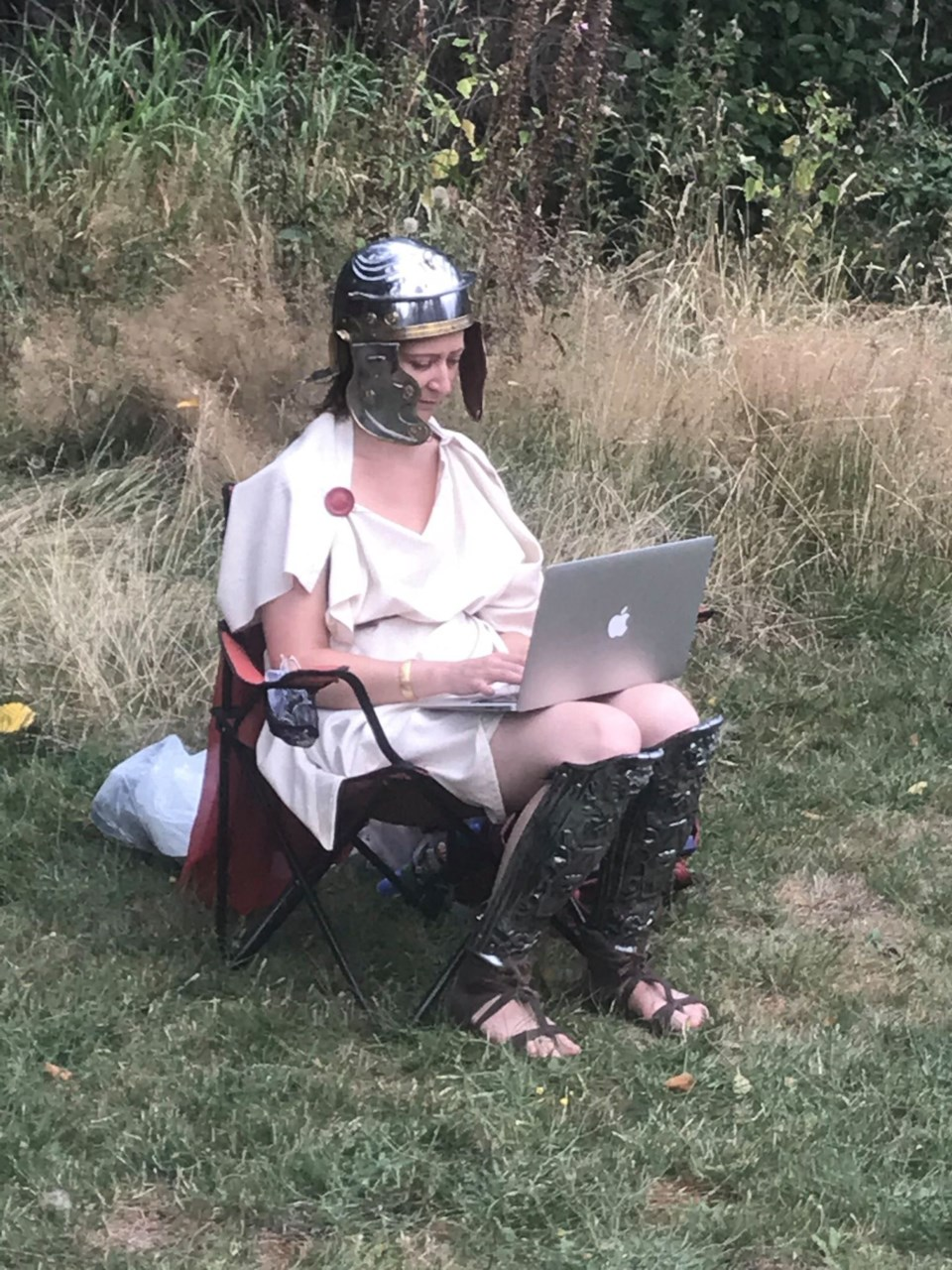 Woman in a winged armoured helmet and Grecian costume sitting in a chair, typing on a mabook