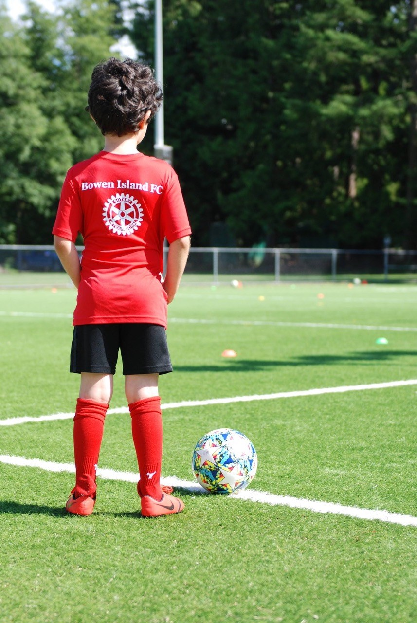 Young child in soccer uniform standing on turf with back to camera and soccer ball in front of them