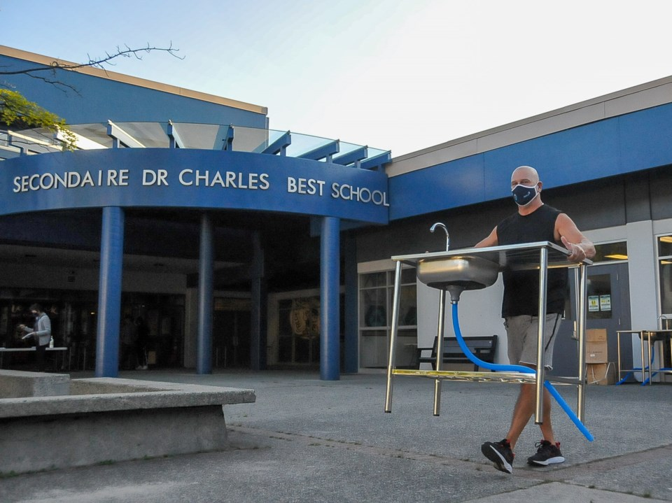Caretaker Dave Leblanc sets up portable handwashing stations around Dr. Charles Best secondary in Co