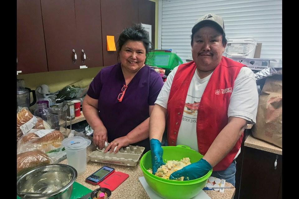 Judy Olson and Chris Landucci work the Nourish program kitchen.