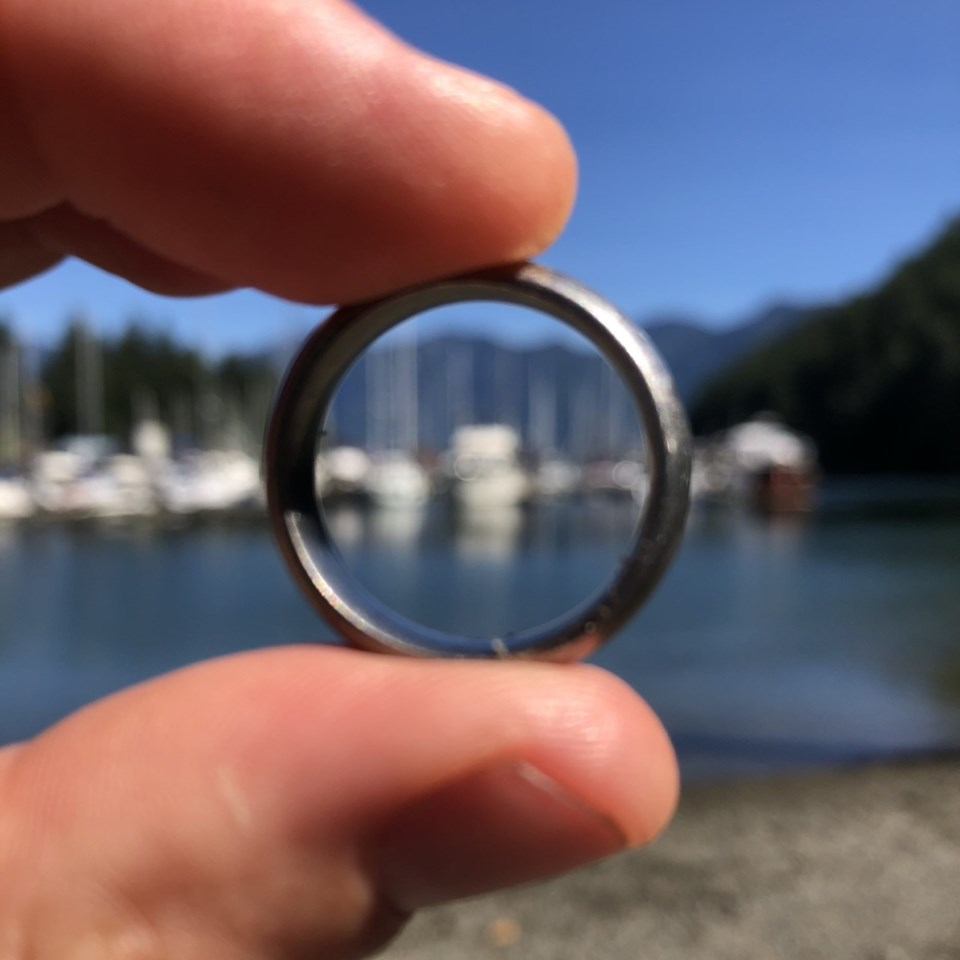 Fingers holding a ring with the boats of USSC Marina in the background