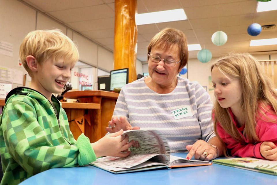 Two BICS children and a grand friend reading a book