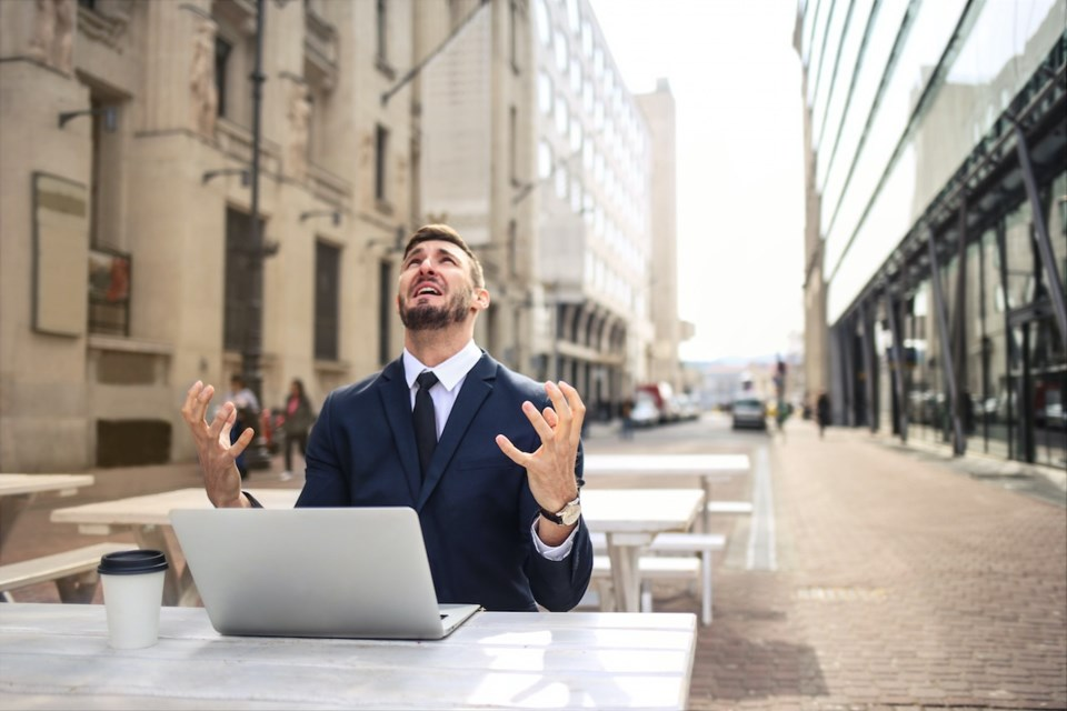 Man looking up at the sky in distress with a computer in front of him