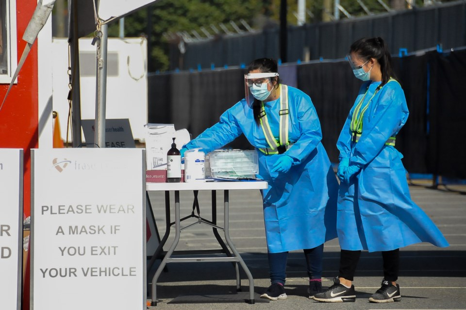 Fraser Health staff wait to greet people at a drive-thru testing site newly opened in Coquitlam this