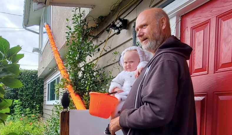 Ray McCurrach with his grandson, Reece Murphy, are ready for Halloween. McCurrach has built a giant candy tube to dispense candy safely during COVID-19.