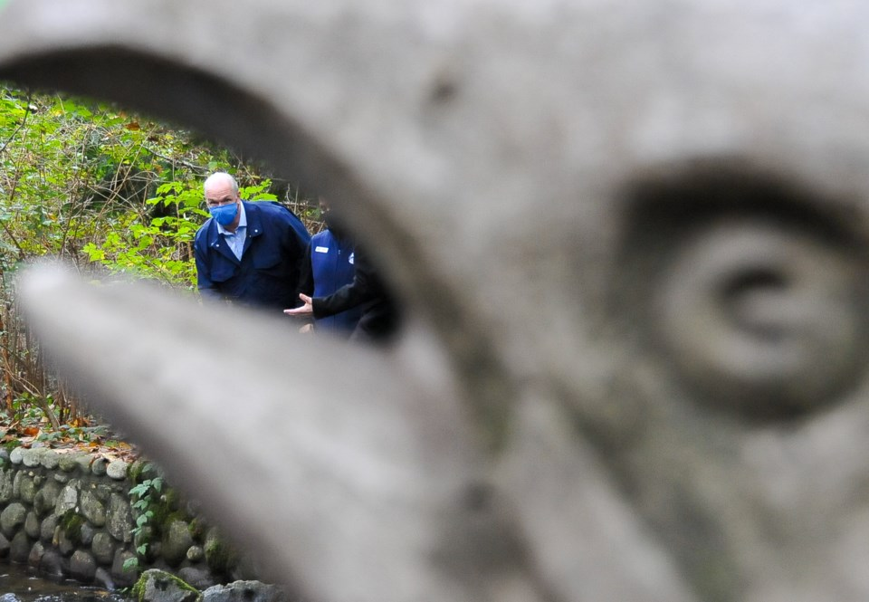 BC NDP Leader John Horgan seen through a statue of a salmon during a visit to Hoy Creek Hatchery in