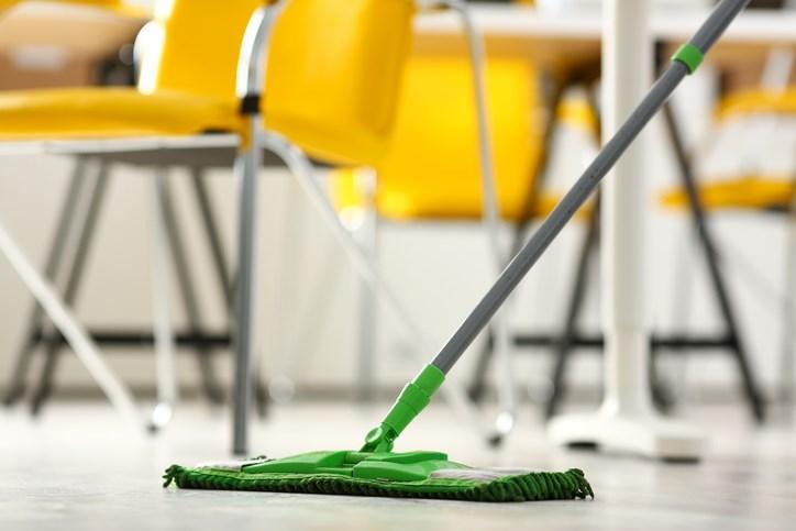 Custodian cleans a school floor.