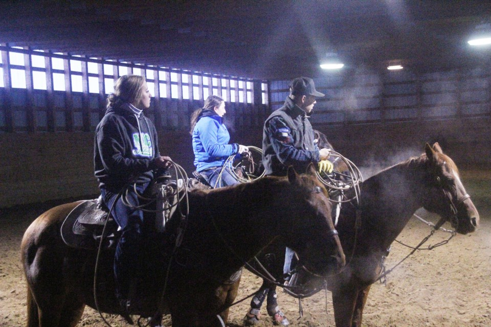 NLC Rodeo Team members try to stay warm while they wait for their turn to ride at rodeo practice on October 21. Though the team has an indoor facility to practice in this winter, blocking out the wind, there is no heat in the building.