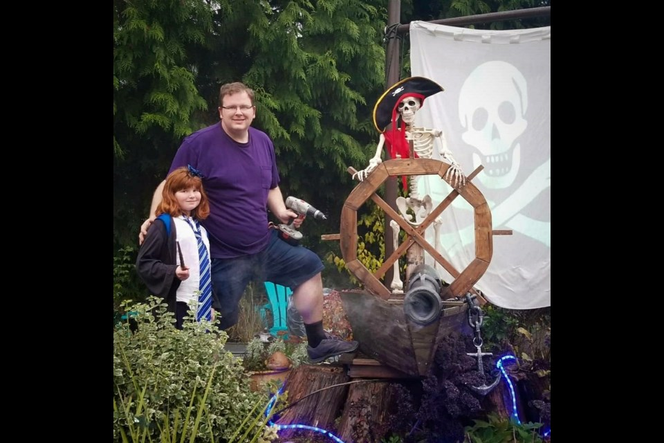 Michael Thomas, shown here with his daughter, built a large Pirates of Caribbean display at his house at 4058 Liverpool Street, complete with projected images, scary sounds and booming cannons.