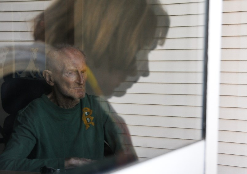 FILE - Brigitte Beurmann waves to her husband Bernie, who suffers from vascular dementia and lives u