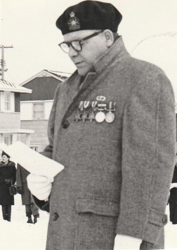 A man reading a speech in an overcoat with medals on his chest