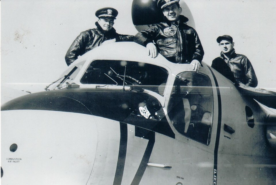 Three men in the cockpit of a plane