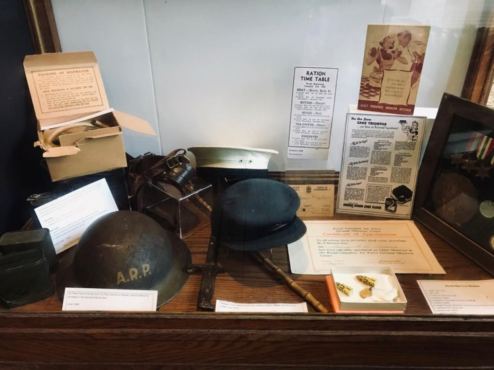 Military caps amid other military artefacts and information