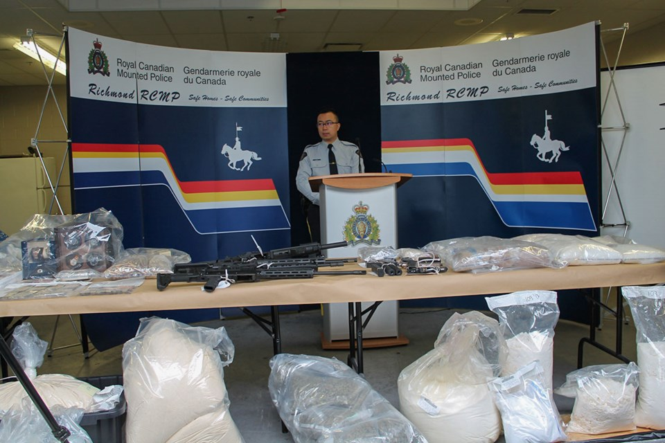 Const. Kenneth Lau, spokesperson with the Richmond RCMP, with various illicit drugs, firearms, cash and high-end items seized from three drug labs in Richmond.