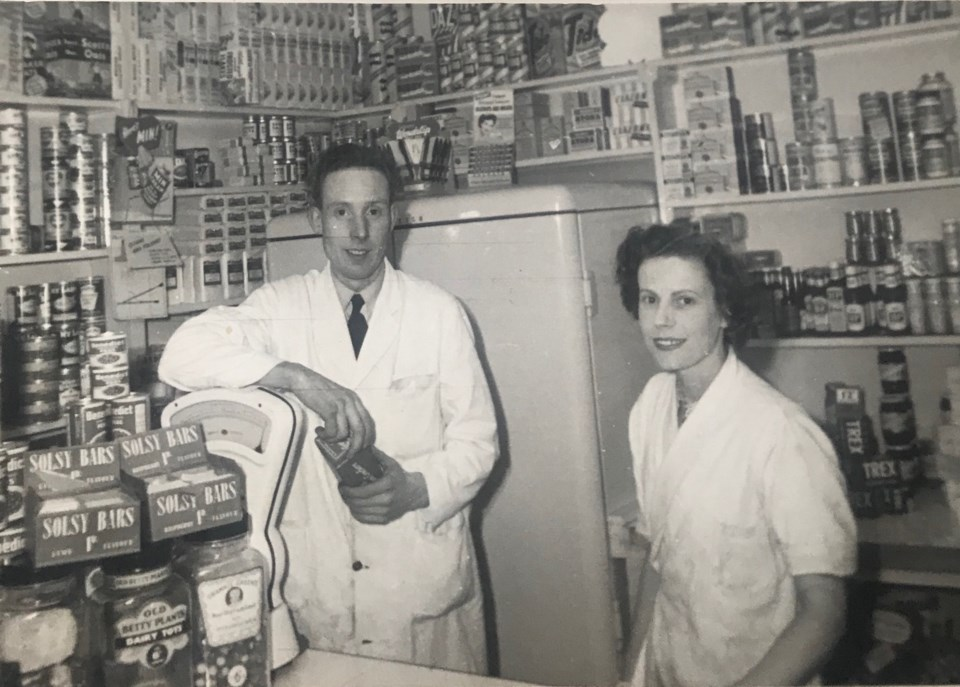 Two people standing at grocery counter - black and white photo