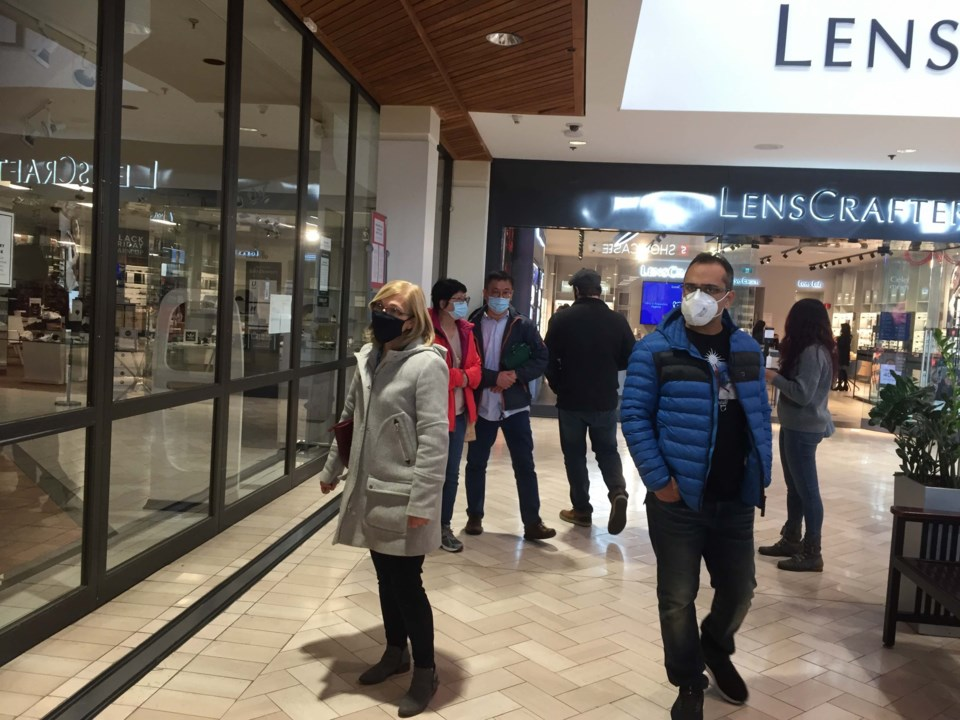 Shoppers peer into the Hudson's Bay at Coquitlam Centre after it was shuttered for failing to pay re