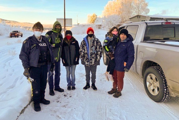 From left: Cst. Robert Drapeau, Gary Bath, Lynn Marchessault, Payton Marchessault, Rebecca Marchessault, and Staff Sergent Tim Marchessault at the Alaska-Yukon border on November 18, 2020. Bath drove from Fort St. John to Pink Mountain to drive Lynne and children to Beaver Creek after the snow storm impeded their trip from Georgia to Alaska to be reunited with Tim.