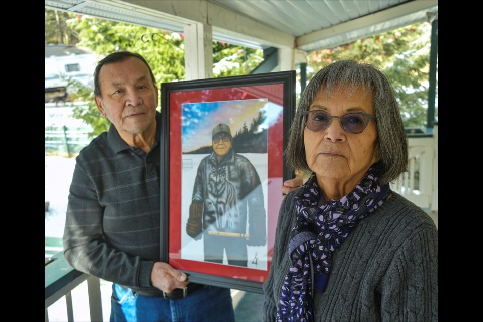 Pete and Muriel Sasakamoose stand outside their home near Pinantan Lake, remembering Pete's brother Fred Sasakamoose, who died on Nov. 24 due to COVID-19 complications. Fred's nephew ,Jordan Sasakamoose, recently painted this portrait of his famous NHLer uncle standing with hockey stick and gloves on Sandy Lake, just steps away from his home northwest of Prince Albert, Sask.