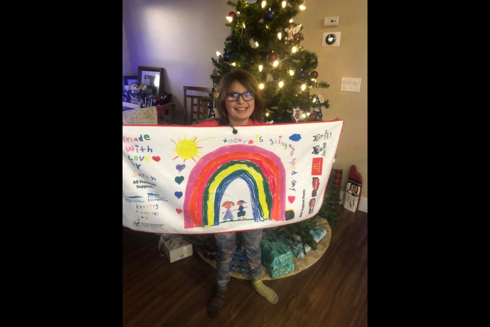 Sarah Byford holds up her custom towel with her own rainbow design.