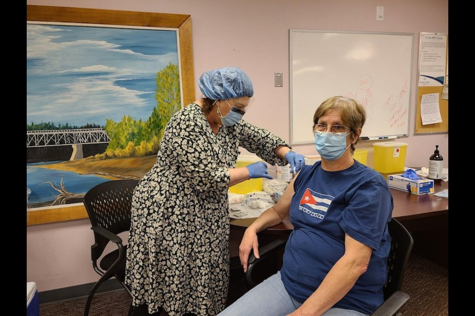 Colleen Bates receives a COVID-19 vaccination from Lynn Fertuck in Fort Nelson.