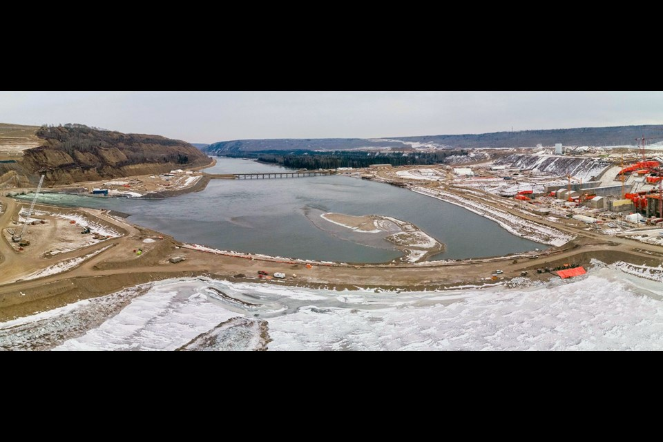 An aerial view of the downstream coffer dam at Site C, January 2021. Both the upstream and downstream cofferdams have been installed across the river and interlocking steel pile walls have been completed.
