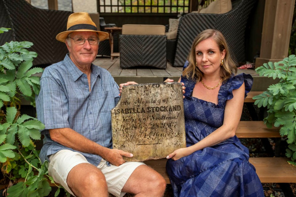 Keith McLaren and daughter Kate Whyte with Isabella Stockand's tombstone, which was removed from Pioneer Park in Victoria and was being used as a stepping stone before ending up in a North Saanich garden. DARREN STONE, TIMES COLONIST