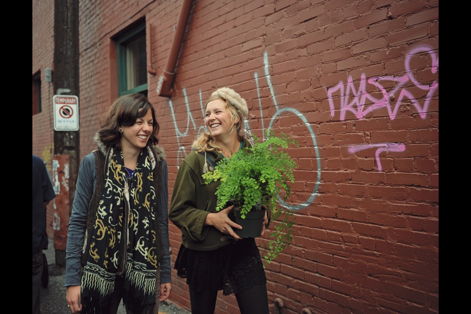 Friends Colby Ferguson (left) and Carly Woolner take home a plant bought from one of the vendors in the Livable Laneway market Sunday afternoon. The alley that runs from East 7th to Broadway Street, just west of Main Street, was turned into an European-style market complete with vendors selling everything from food to jewelry, and musical performances.