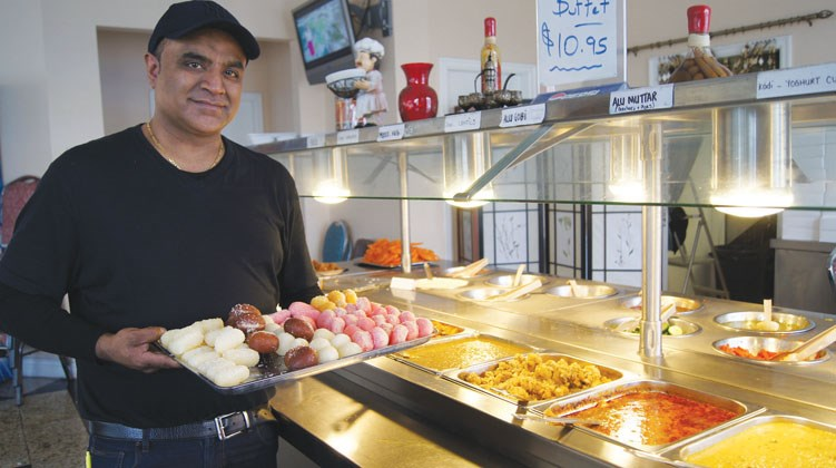 Graeme Wood/Special to the News Sarb Pabla, manager of Himalaya Restaurant, displays his popular Indian food buffet during the lunch hour crunch.