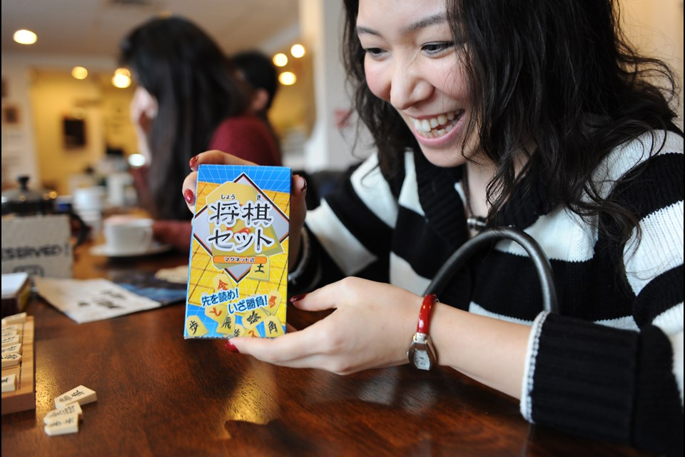 Keiko Minato shows off her miniature shogi travel game she purchased during a recent trip home to Japan. Photo by: Rebecca Blissett