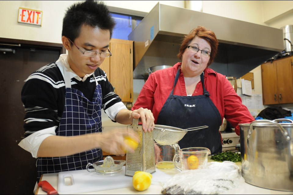 Chef April Pringle and a volunteer prepare Marpole Place's Thursday night community dinner at St. Augustine's Anglican Church. Photo: Dan Toulgoet