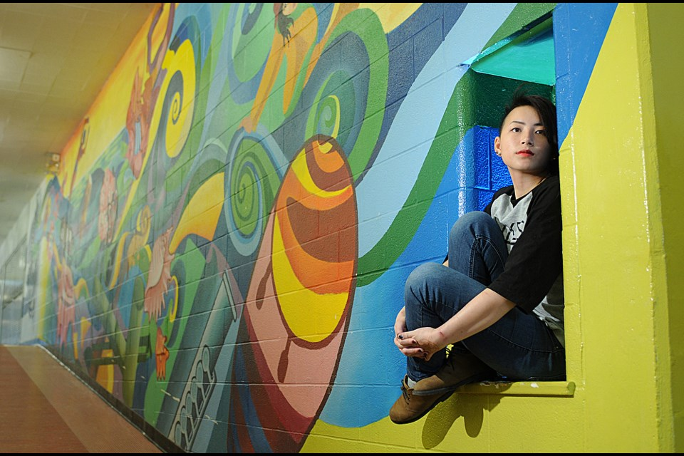 David Thompson secondary school's Karen Tong is one of the students beautifying school walls with colourful murals. Photo: Dan Toulgoet
