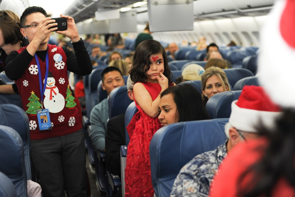 Most of the young passengers aboard the Air Transat flight to the North Pole to find Santa Thursday afternoon peered down aisles and peeked over seats to get a glimpse of the man in the red suit. Photograph by: Rebecca Blissett