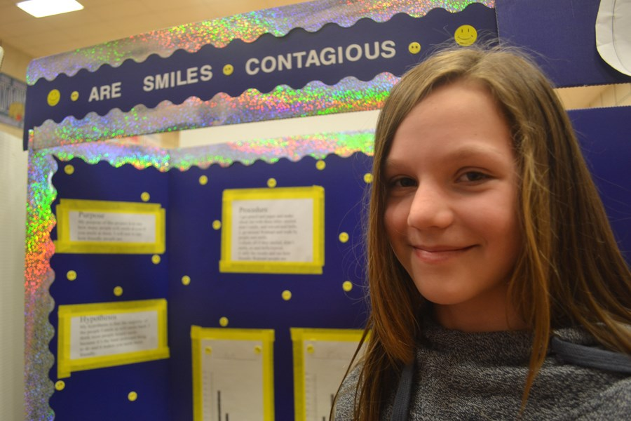 Emily Jobson, age 12, presenting her research on whether or not smiles are contagious with a demonstration.