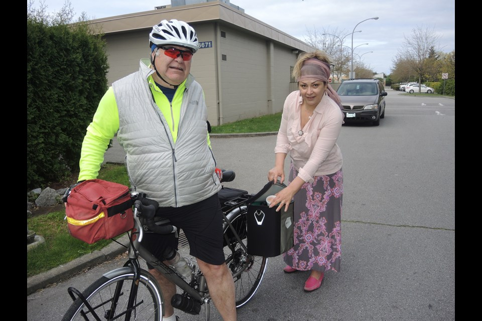 Ecaterina Grisacova, who works for the Richmond Society for Community Living, assists Keith Lang with his meals on bikes delivery. Grisacova is also a volunteer for Meals on Wheels, a program that assists shut-ins with a healthy meal and a friendly visit. May, 2015.
