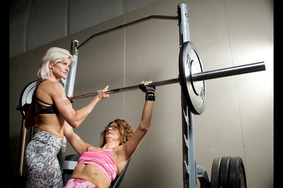 Writer-turned-competitive bodybuilder Jenn Farrell works out with her trainer Yelena Yermolenko. Yermolenko believes every woman who exercises should compete to provide the extra motivation to see what she can achieve. Photo Jennifer Gauthier