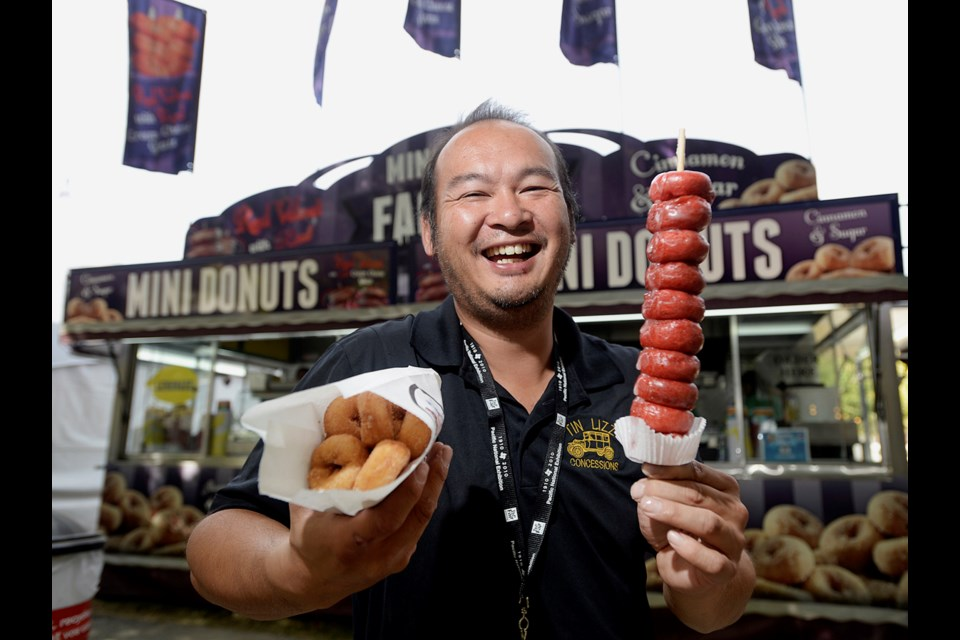 Jason Au of the Mini Donut Factory shows off red velvet mini donuts with cream cheese glaze. The tasty, artery clogging treats are available at this year's PNE. Photo Jennifer Gauthier.