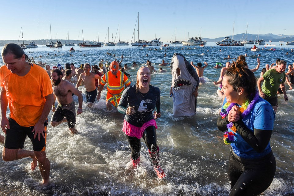 At least three thousand people braved the frigid waters of English Bay, January 1st, 2016, for the Vancouver Polar Bear Swim Club's 96th annual dip. Photograph by: Rebecca Blissett