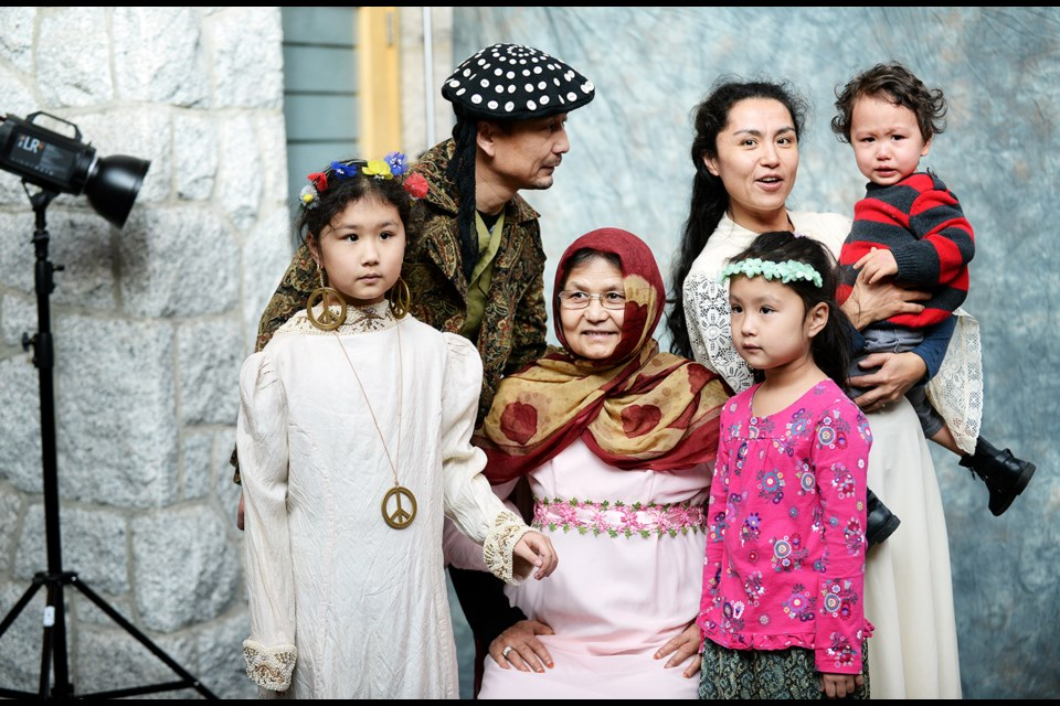 Arzu Imin, at right, and family get their portrait taken at Shadbolt Centre during an Art on the Spot Family Portraits event on Saturday, Feb. 6.