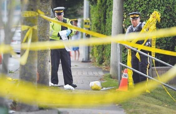 Police survey the scene on No. 5 Road near Highway 91, where a 64-year-old cyclist was killed in September 2013