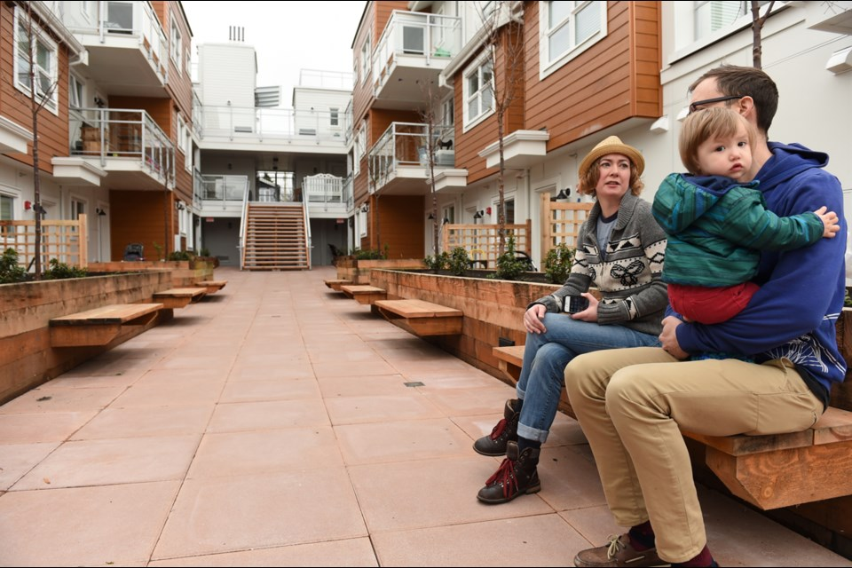 Taryn Griffiths chats with Ben Ernst and his 13-month-old daughter Margot Dempsey–Ernst in the courtyard of the city's first cohousing complex, which is located in East Vancouver's Kensington-Cedar Cottage neighbourhood. Photo Dan Toulgoet