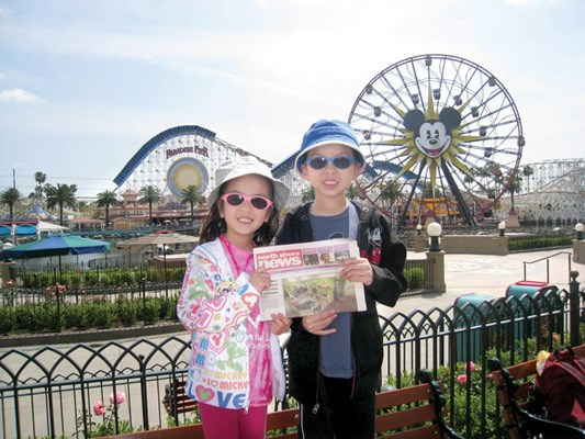 Christina and Alastair Quon sport hats and shades in the sun at Paradise Pier in Disney's California Adventure Park.