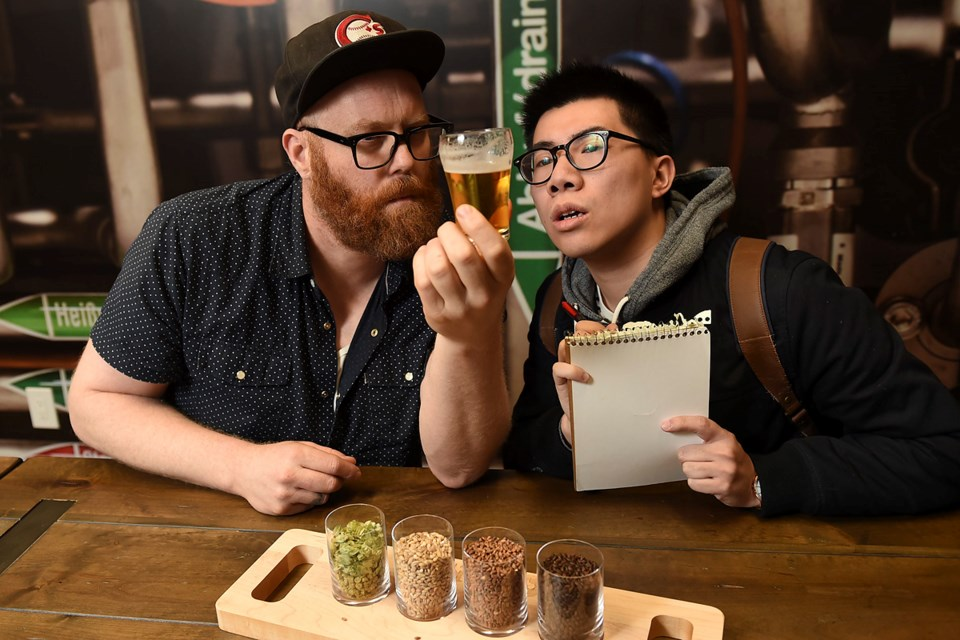 Brewmaster Caleb Colten (left), who is heading up the VSB's Craft Fermentation Sciences pilot program, gives prospective student Kennedy Yeung a lesson in brewing techniques. Photo Dan Toulgoet